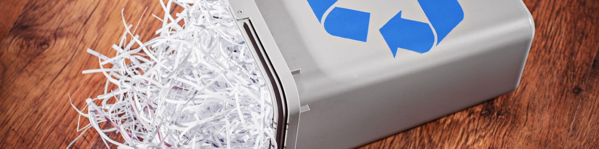 Flipped recycle bin full of shredded paper on a wooden floor